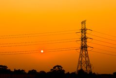 Sunset and tree high voltage. Silhouette of columns and high voltage wires In natural environment, There is a sunset background and the sun is between two wires stock image