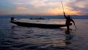 Fisherman on Inle Lake, Myanmar. The sunset trip on Inle Lake is the best choice to enjoy the unique technique of local fishermen - they show their skills of leg stock video footage