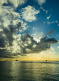 Sunset on a tropical beach in the caribbean. With cloudy skies and flat calm waters Royalty Free Stock Photography
