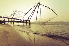 Sunset at tropical beach with chinese fishing nets Royalty Free Stock Images