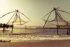 Sunset at tropical beach with chinese fishing nets. Sunset at tropical beach. Ocean coast landscape with chinese fishing nets silhouette at Cochin (Kochi). South Stock Photo