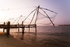 Sunset at tropical beach with chinese fishing nets. Sunset at tropical beach. Ocean coast landscape with chinese fishing nets silhouette at Cochin (Kochi). South Stock Image