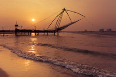 Sunset at tropical beach with chinese fishing nets. Sunset at tropical beach. Ocean coast landscape with chinese fishing nets silhouette at Cochin (Kochi). South Royalty Free Stock Photos