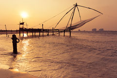 Sunset at tropical beach with chinese fishing nets. Sunset at tropical beach. Ocean coast landscape with chinese fishing nets silhouette at Cochin (Kochi). South Stock Images