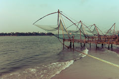 Sunset at tropical beach with chinese fishing nets. Ocean coast landscape with traditional Indian boat and chinese fishing nets at Cochin (Kochi). South India Royalty Free Stock Images