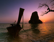 Sunset at tropical beach landscape with Thai traditional boat an. D tree. Rock formation island silhouette under evening sun at ocean coast . Pranang cave beach Stock Images