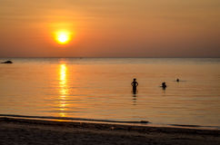 Sunset at tropical beach with silhouettes Royalty Free Stock Image