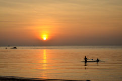Sunset at tropical beach with silhouettes Royalty Free Stock Photography
