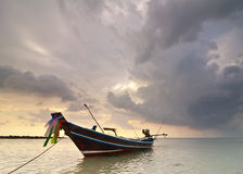 Sunset at tropical beach with Thai fishing boat Stock Photo