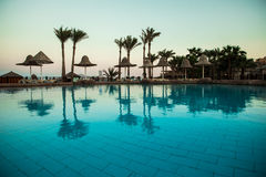 Sunset at the tropical swimming pool. Summer vocation Stock Photos