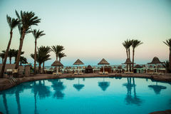 Sunset at the tropical swimming pool. Summer vocation Stock Images