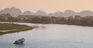 Sunset in the Tropics. Colorful light fills the surrounding areas of Ninh Binh in Vietnam with bright orange colors as a boast passes along the river Royalty Free Stock Photos