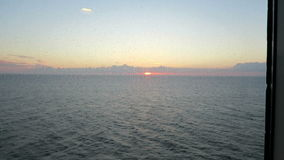 Sunset trough the window of ferry. baltic sea. raindrop marks on window stock video footage