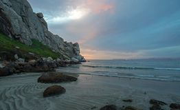 Sunset twilight colors and sand swirls at Morro Rock on the central coast of California at Morro Bay California USA royalty free stock photo
