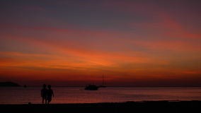 Sunset with the two childrens silhouettes playing at the shore. Two kids playing at the sunset beach by the dawn, amaizing sky with the boat on the sea Royalty Free Stock Photos