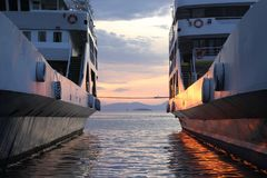 Sunset in between two ferries at Igoumenitsa, Greece. Sunset between two ferries in Igoumenitsa port, Greece. low sun and ferry in a cloudy sunset. Warm orange Royalty Free Stock Image