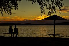 Sunset. Two people are sitting on a bench on the beach and watching the sunset in summer Royalty Free Stock Photos