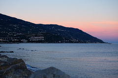 Sunset at the Tyrrhenian Sea. Houses are located on a hillside mountain Royalty Free Stock Image