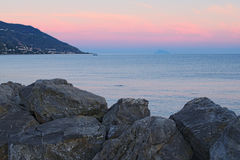 Sunset at the Tyrrhenian Sea. Large stones in the foreground. Marina di Patti. Sicily Stock Photos