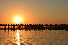 Sunset U Bein bridge in Amarapura, Mandalay, Myanmar. U Bein bridge is a crossing that spans the Taungthaman Lake near Amarapura in Myanmar. The 1.2-kilometre Royalty Free Stock Image