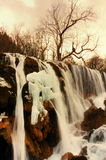 Sunset under the ice waterfall. China Jiuzhaigou sunset under the ice waterfall Royalty Free Stock Images