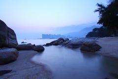 Sunset under long exposure along seashore Stock Photo