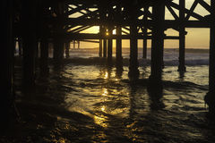 Sunset under a pier Stock Photos