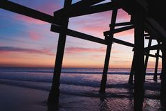 Sunset under a pier in california coast royalty free stock images