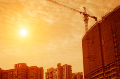 Sunset under the site tower crane. Sunset on the construction site tower crane work stock photo
