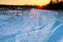 Sunset under snow country road Royalty Free Stock Image