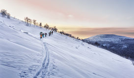 Sunset at the Ural ridge, a group of skiers on the slopes. Photo taken during the ski trip in January 2017 in the Northern Urals. Sunset, the group goes skiing Royalty Free Stock Image