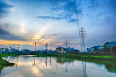 Sunset in urban areas. Featuring transmission towers, ponds that make beautiful reflection, crane, rays of light and many houses Stock Photography