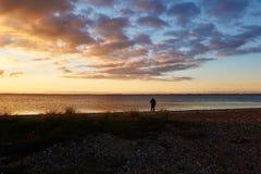 Sunset at Vadum Beach in Salling, Denmark - series. Colorful sunset at Vadum beach in Salling, Denmark. Man walking the dog at the beach Stock Photo