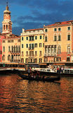 Sunset in Venice. Venice, Italy- July 29th, 2011: Image of a gondola with tourists sailing at the sunset in front of a traditional building on The Grand Canal Stock Photo