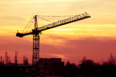 Sunset in vibrant colors and a crane in industrial area Stock Photos