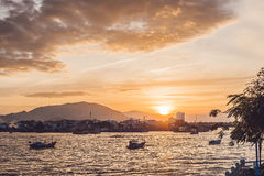 Sunset in Vietnam, sea, small houses and Vietnamese boat Stock Photos