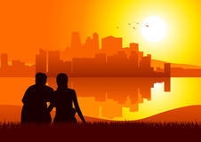Sunset View. Silhouette illustration of a couples sitting on grass watching cityscape during sunset Stock Photo