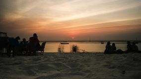 Sunset view of african beach with resting people groups, timelapse stock footage