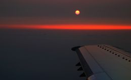 Sunset View From Airplane. Sunset over airplane flying in clouds Stock Image