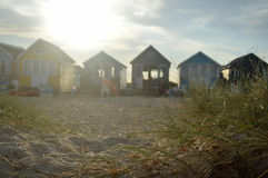 Sunset view of beach huts with sand and grass in foreground Royalty Free Stock Photos