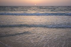 Sunset view from the beach. View of the waves from the beach after sunset. The sky is purple and orange royalty free stock photography