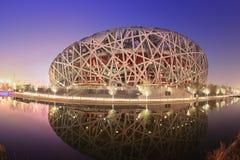 Sunset view of Beijing stadium reflected in lake Royalty Free Stock Photos