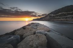 Sunset view from a breakwater on the beach royalty free stock photo