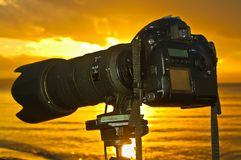 Sunset seashore view of a camera on a tripod. Sunset view of a camera with a telephoto lens on a tripod at a shoreline of a northern beach with gold reflexions Stock Photo