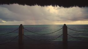 Sunset view of Caribbean sea and rainbow from wooden pier, Punta Cana resort. Sunset view of Caribbean sea and tropical beach from wooden pier, Punta Cana resort stock video footage