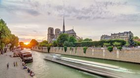 Sunset view of Cathedral Notre Dame de Paris timelapse in Paris, France. View from Bridge of the Archbishopric. Boat station and embankment. Architecture and stock video footage