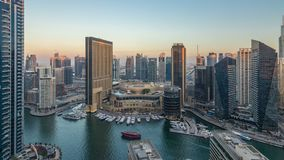 Sunset view of Dubai Marina evening aerial timelapse, UAE. Modern skyscrapers and residential buildings with orange light. Yachts and boats near shoping mall stock video