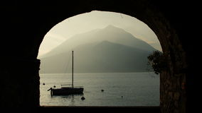 Sunset view of the lake in Lombardy. Varenna, Lake Como, Italy. Boat on Lake Como at the sunset, mountain in the background, view through arch. Varenna, Lake stock video footage