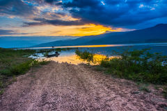 Sunset view at lake. Sunset view at the lake with mountain background. The dirt road over water by flood Royalty Free Stock Photography