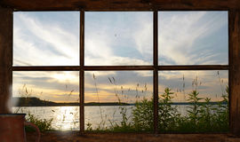 Sunset view of the lake out the cottage window. Stock Photos